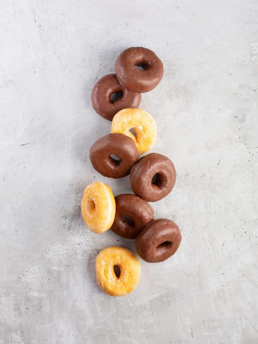 Group of glazed and chocolate donuts on gray background